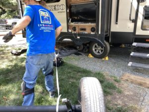 A man pulling an axle towards the side of an RV