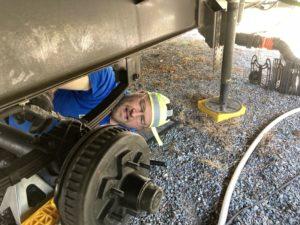 A man under an RV repairing a wheel.