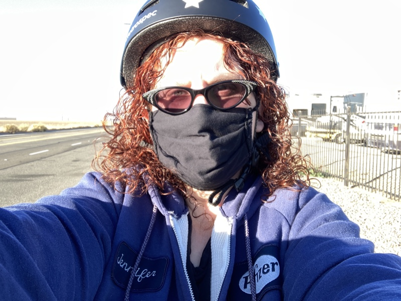 A light skinned person in a mask and  bike helmet looking at the camera