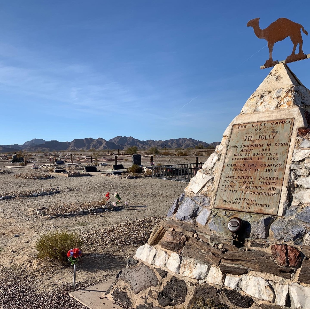 A stone pyramid monument with blue skies and a cemetery in the background