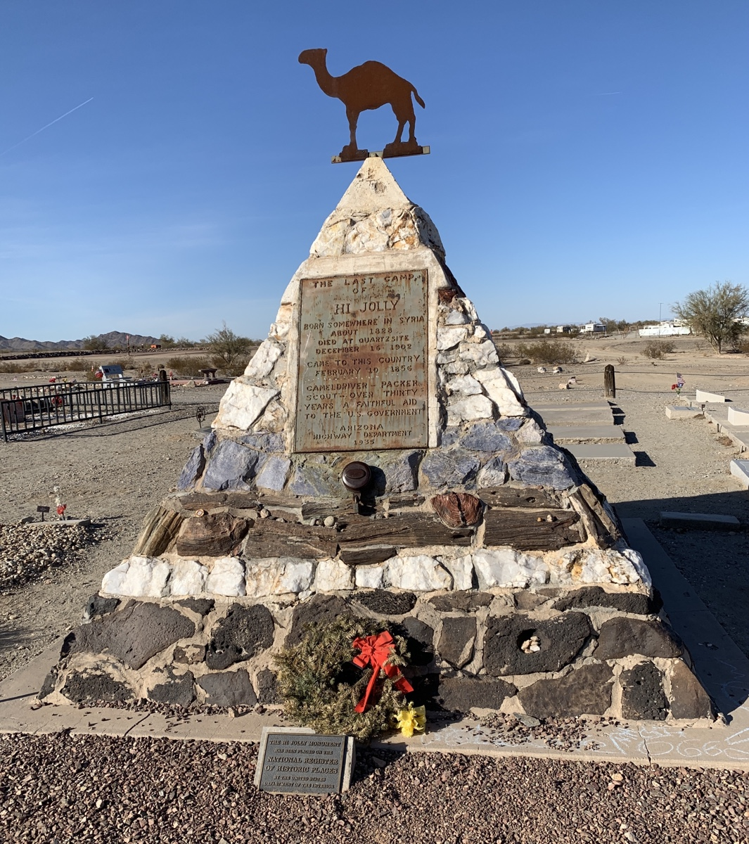 The Hi Jolly monument,  a stone pyramid with a metal camel on top and a plaque