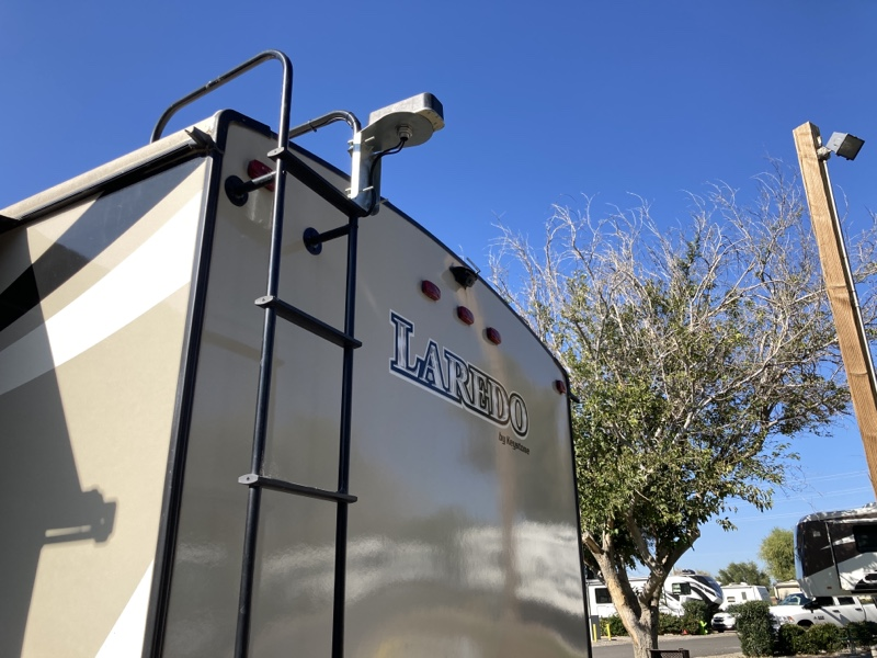 The rear end of a travel trailer with a brick shaped antenna mounted to the ladder.