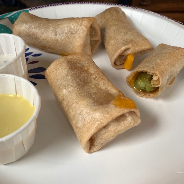 pickles rolled in tortillas like an egg roll or mini burrito. with two dip cups.
