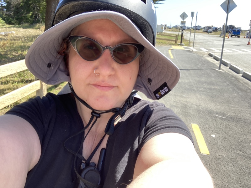 a light-skinned fat person wearing a large sunhat under a bike helmet and sunglasses