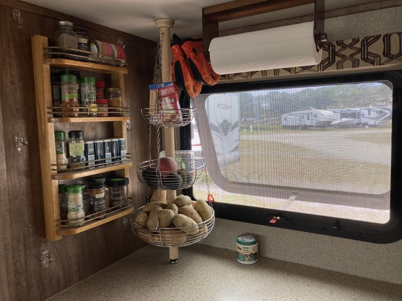 A wooden spice rack mounted to a wall next to a counter and window. There is a three tiered basket with potatoes, avocados, and supplement bottles between the window and rack.