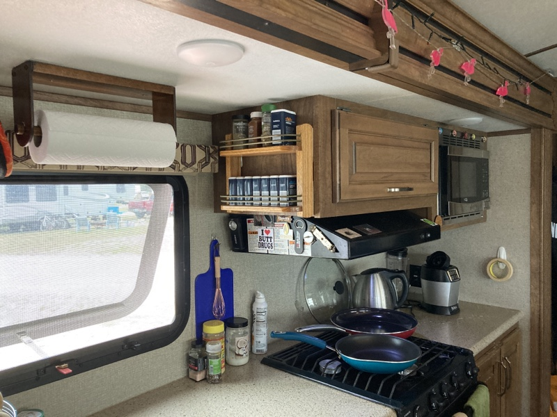 An RV stove with a small spice rack mounted in the cabinet above the stove. There are two frying pans on the stove and a few odds and ends on the counter.
