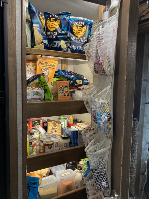 A 4 shelf pantry filled with food. There is a shoe rack hanging on the door for snacks and stuff