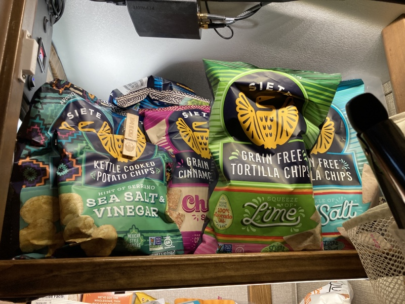A shelf full if different varieties of Siete chips  the sea salt and vinegar bag of potsti chips has an embossed clothespin keeping it closed